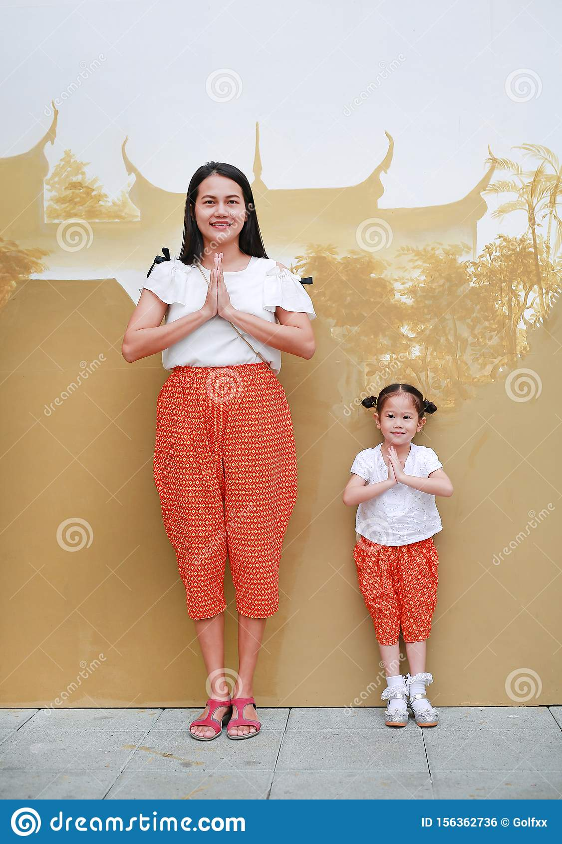 Portrait of asian mother and child girl in traditional thai dress praying. Sawasdee is meaning hello