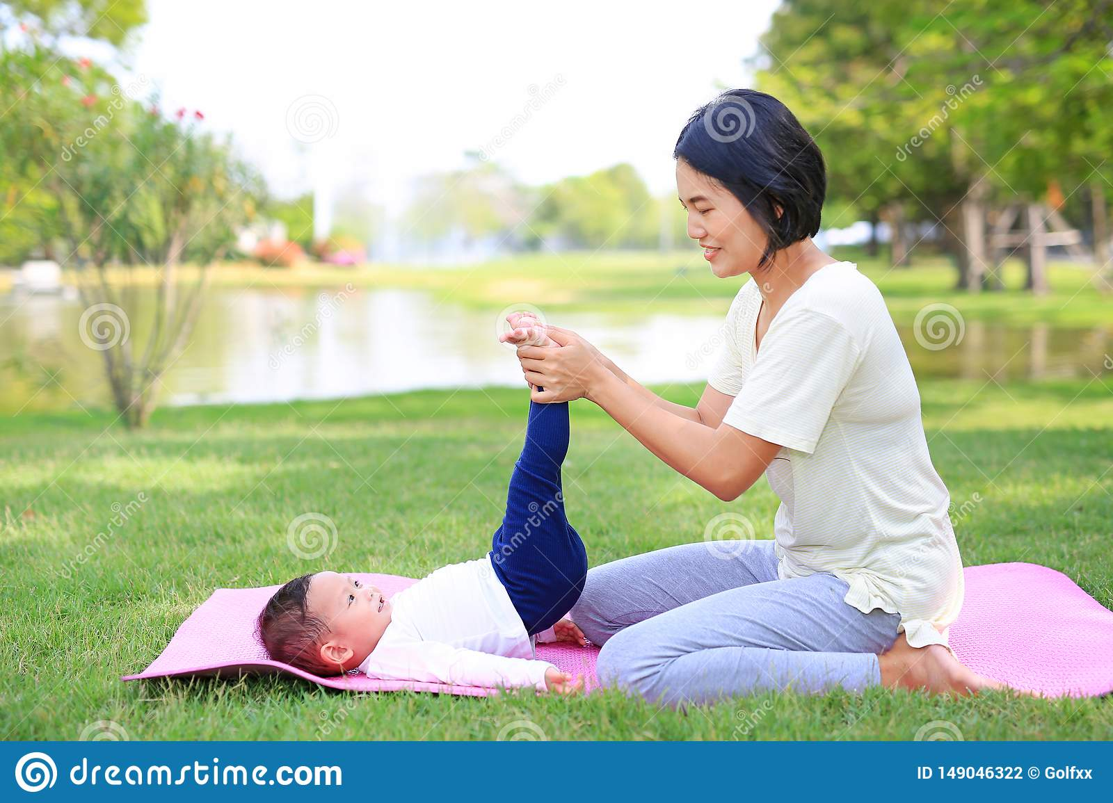 Portrait of Asian mother doing baby yoga for her son on green lawn in the nature garden outdoor