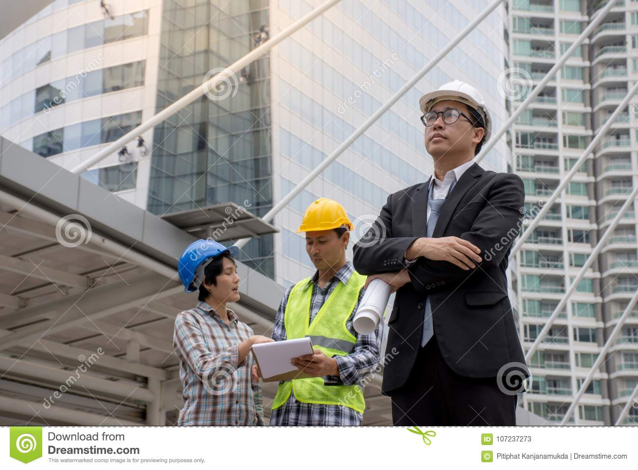 Portrait of a Asian serious engineer wearing safety helmet architects discussing construction plan