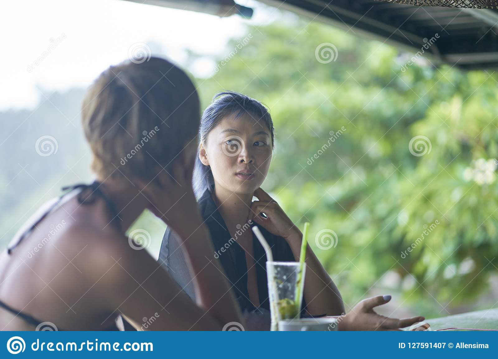 Portrait of 2 asian women chatting, drinking & smiling at beach bar in summer
