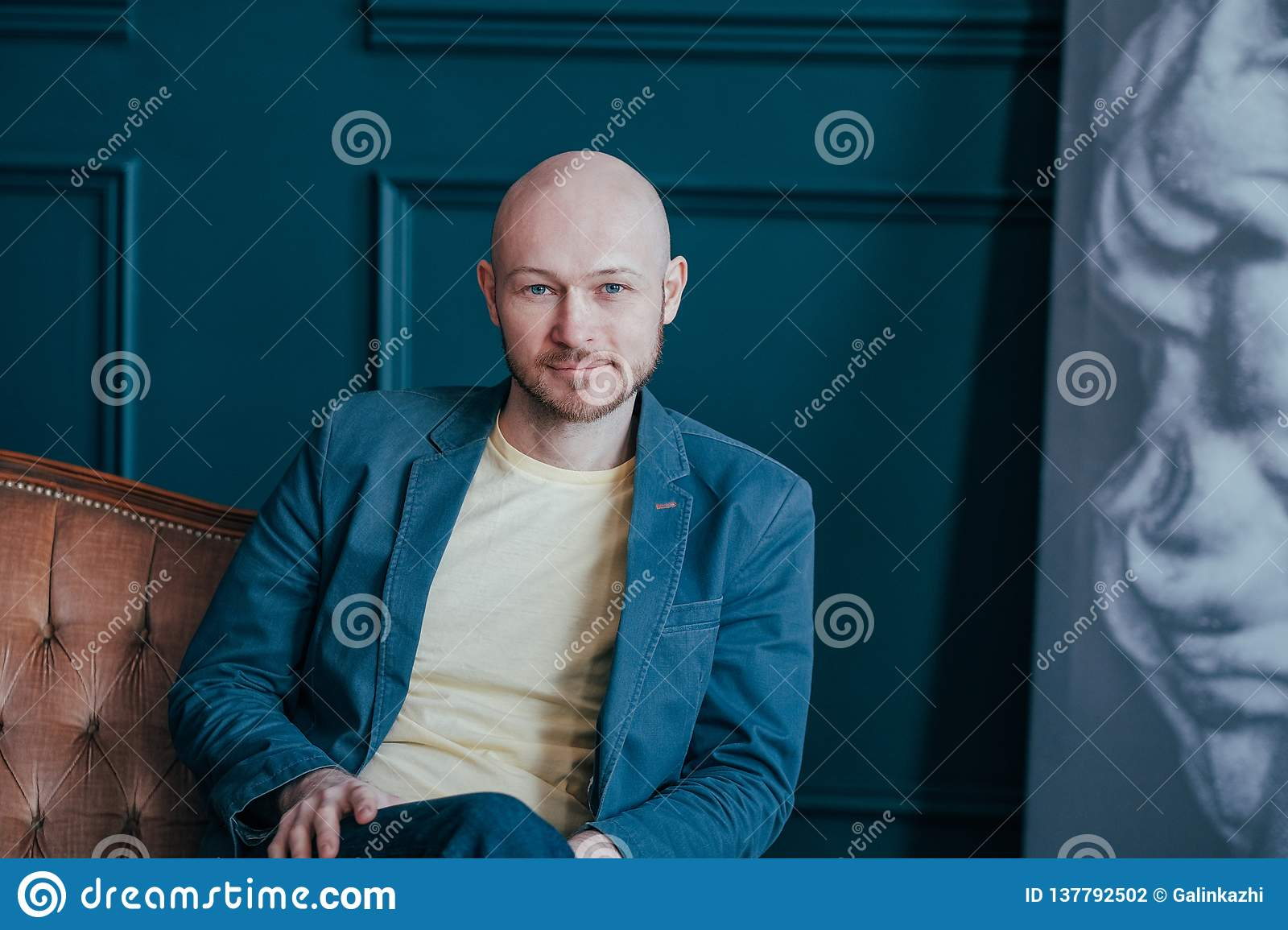 Portrait of attractive adult successful bald bearded man in suit on rich interior blue background