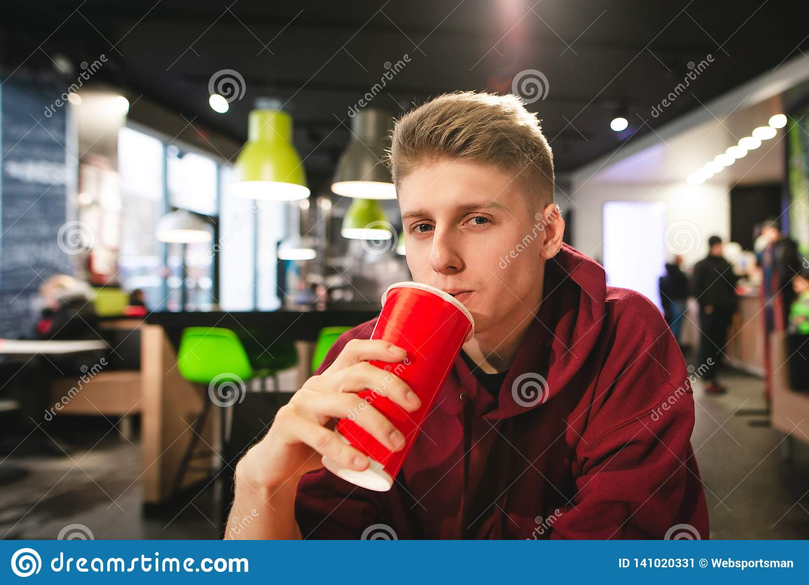 Portrait of attractive boy with a large red glass in his hand, drinking a stake and looking at the camera