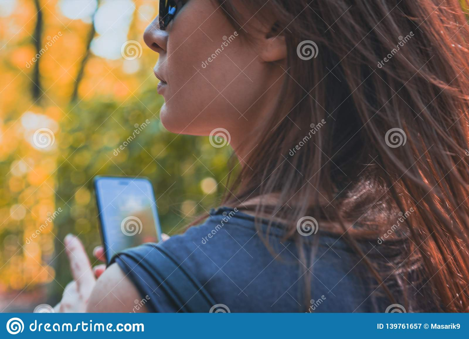 Portrait attractive of a brown-haired woman with a phone in her hand for a walk. Toned