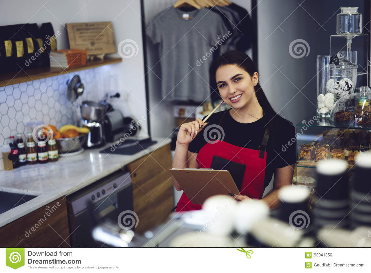 Portrait of attractive female barista working in cafeteria