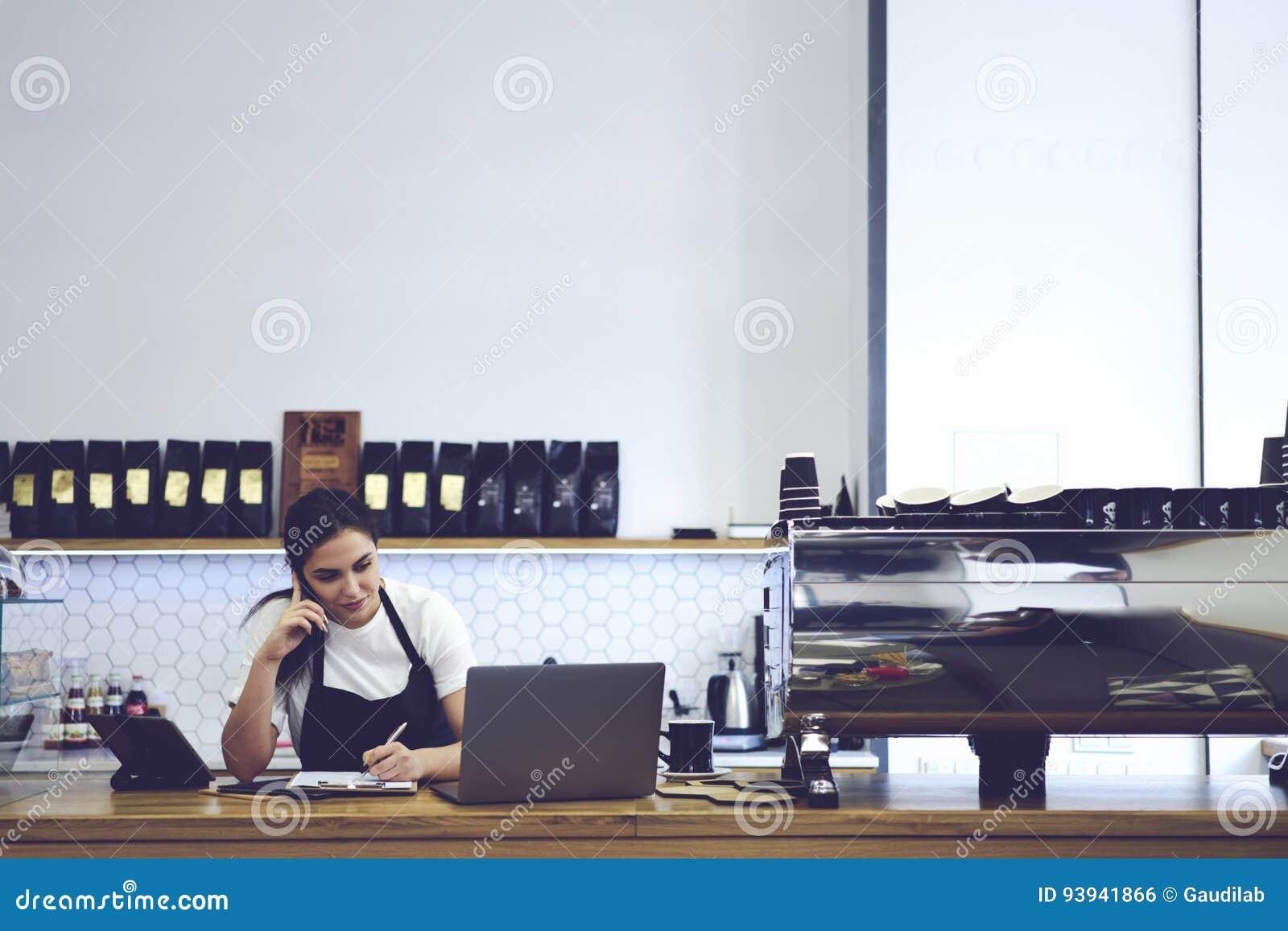 Portrait of attractive female barista working in cafeteria