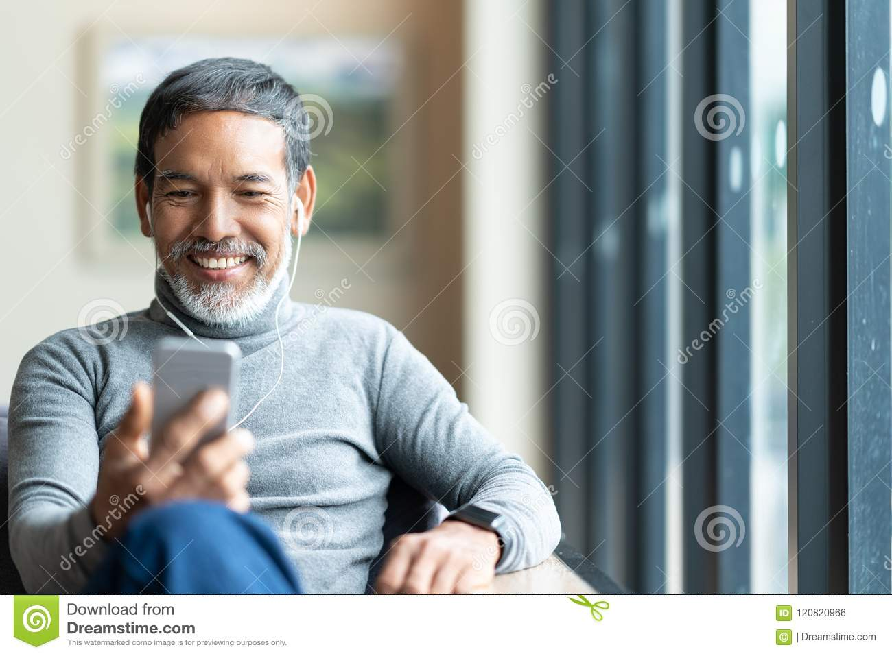 Portrait of attractive mature asian man retired with stylish short beard using smartphone sitting or listening music