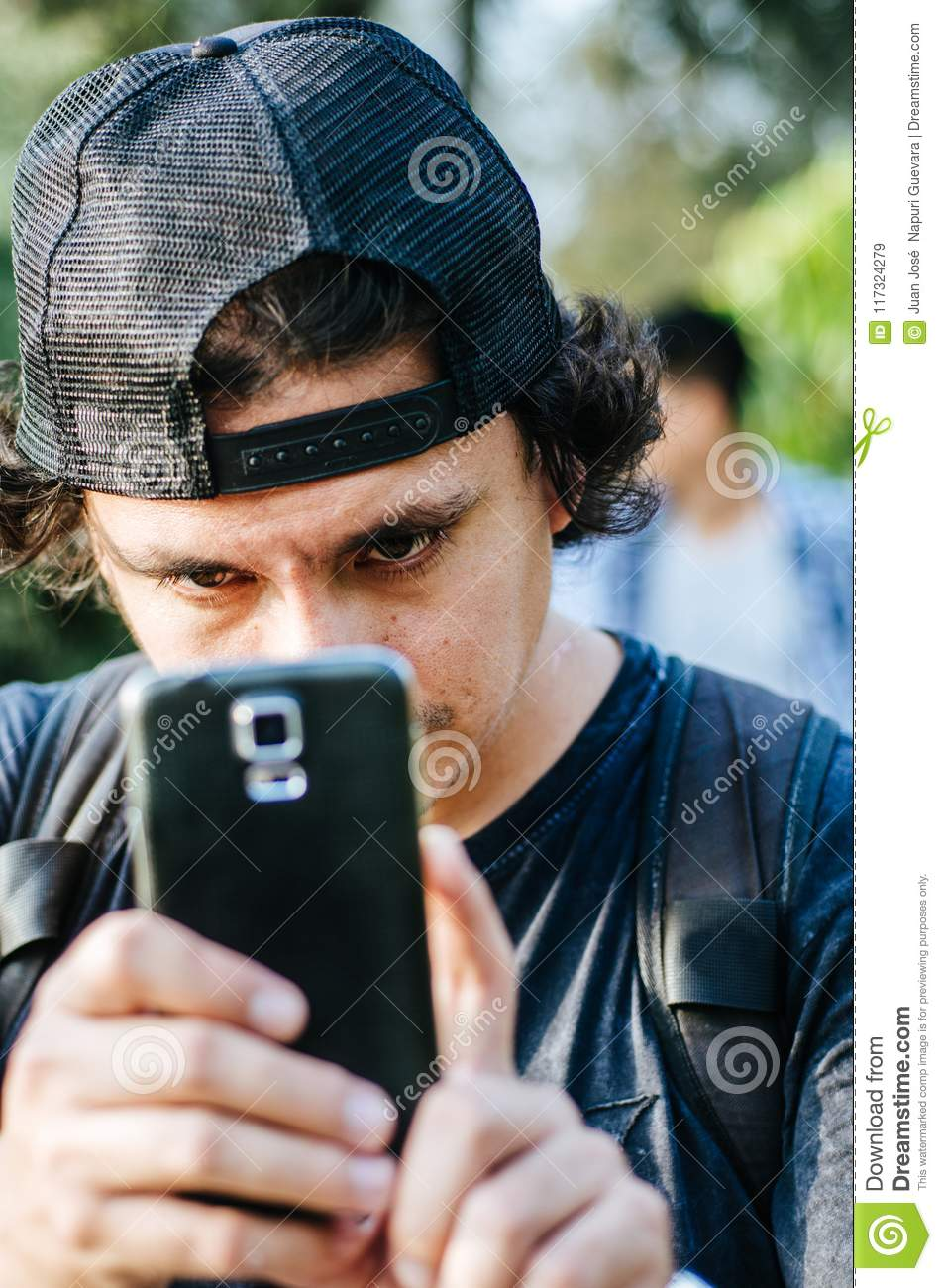 Portrait of an attractive teen boy holding his smartphone with his hand and take photograph.