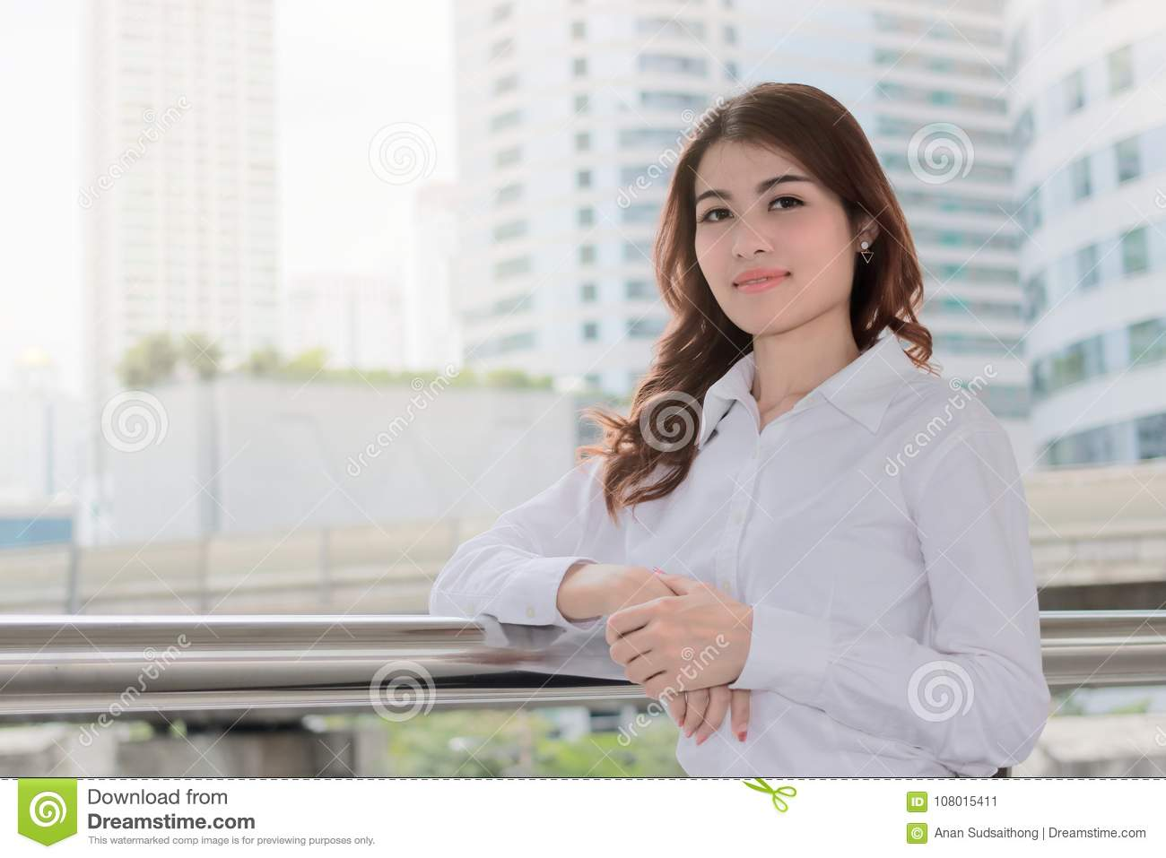 Portrait of attractive young Asian businesswoman looking on camera at urban building with sunshine effect background. Leadership w
