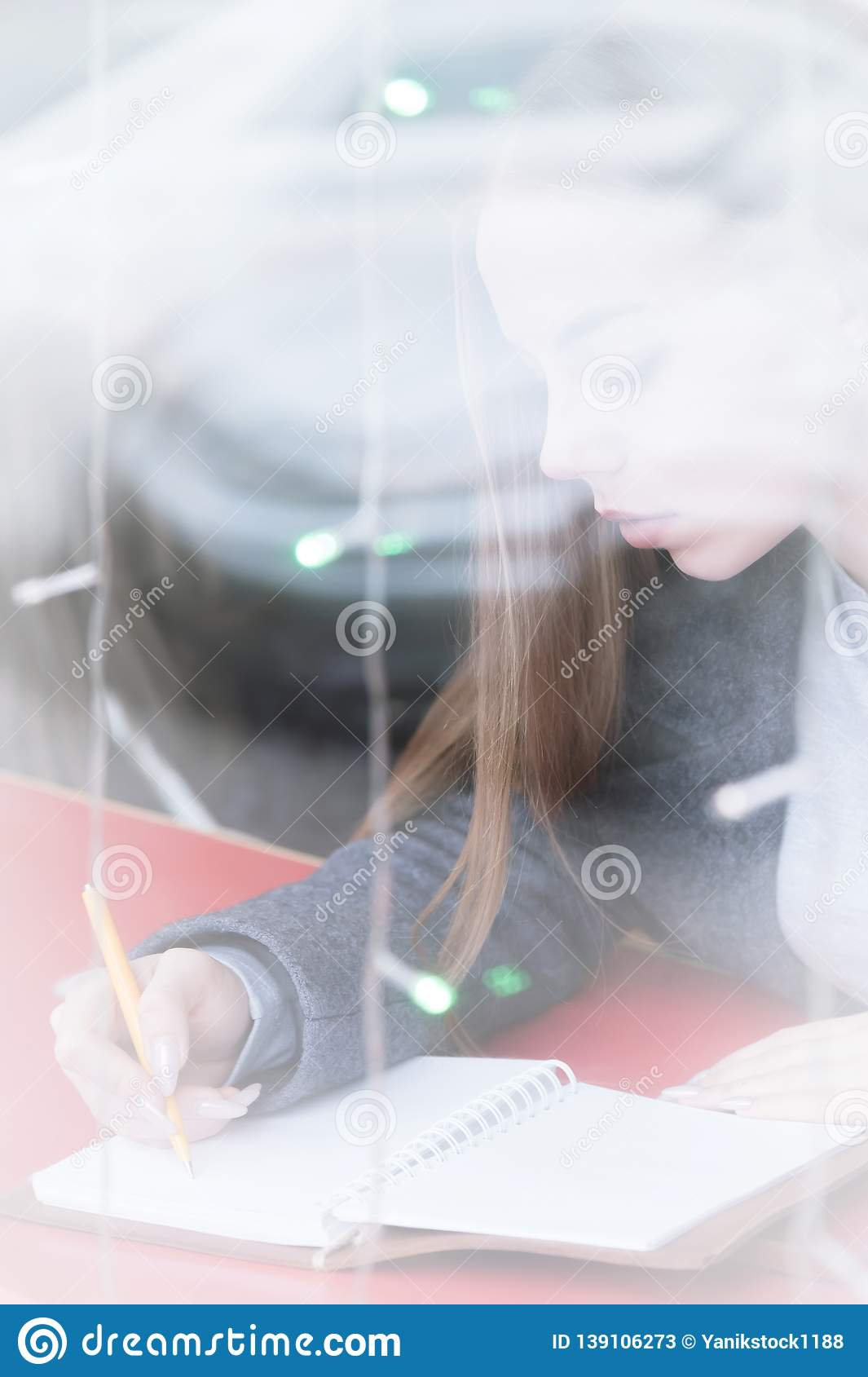 Portrait of an attractive young journalist girl with pen and notepad in cafe behind the showcase. Non-contrast view