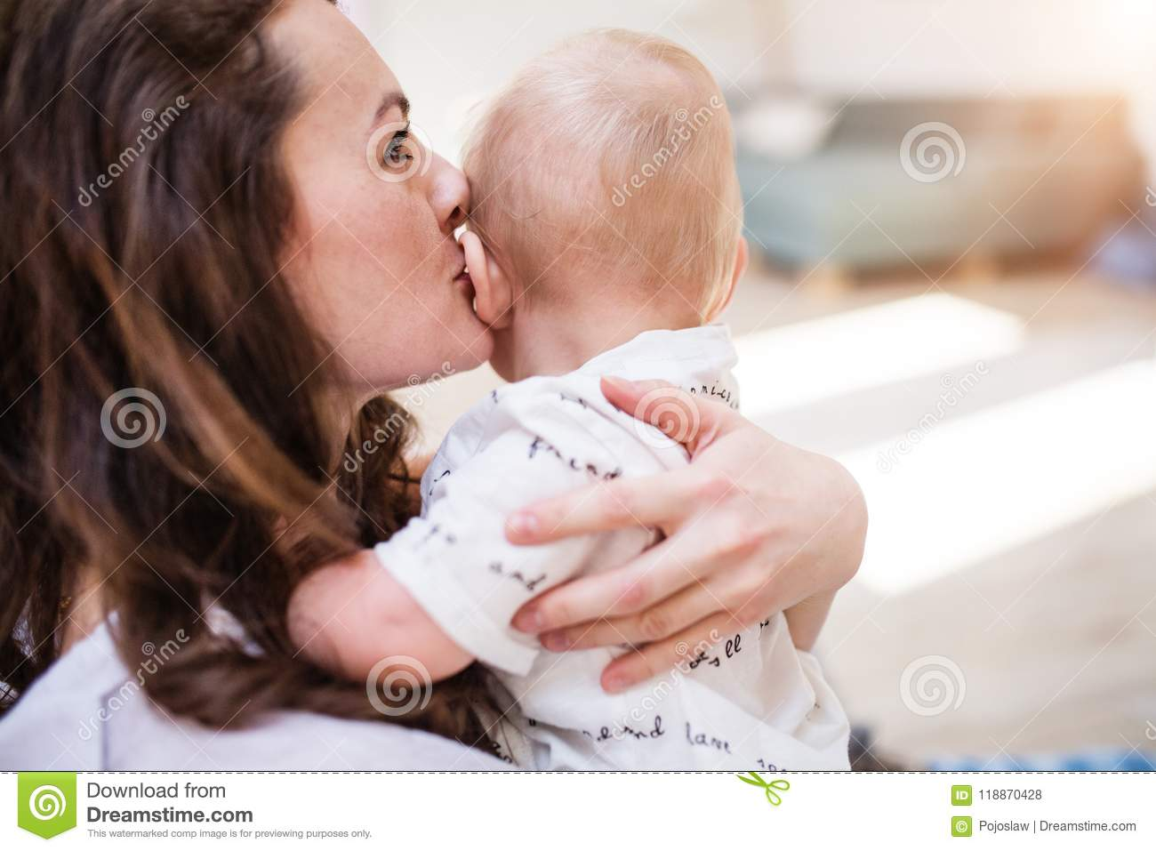Portrait of a young mother kissing her baby son at home. Close up.