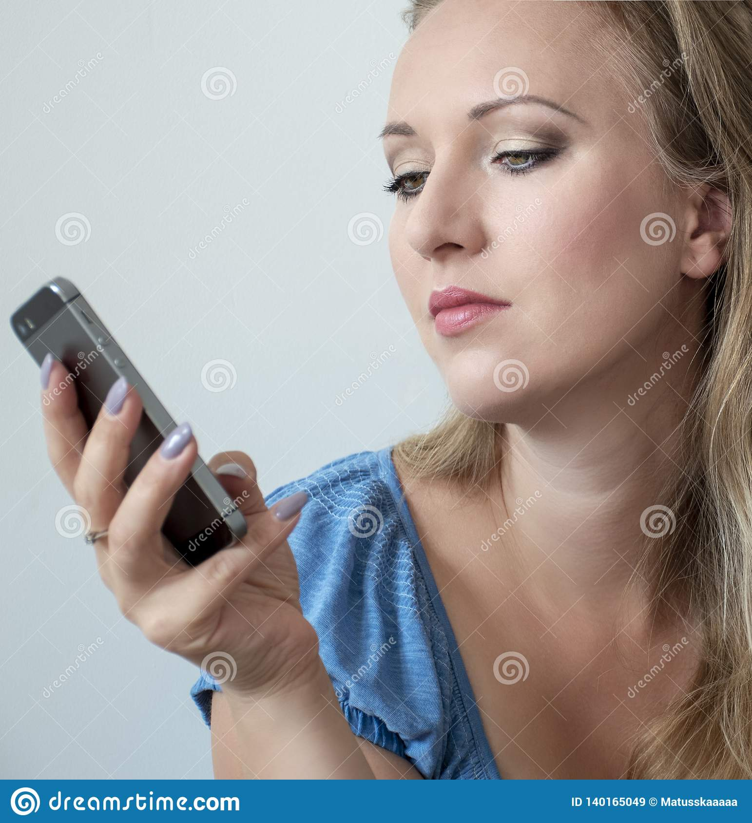 Portrait of attractive young woman looking on the phone. Pretty woman with green eyes and long blonde hair holding smartphone