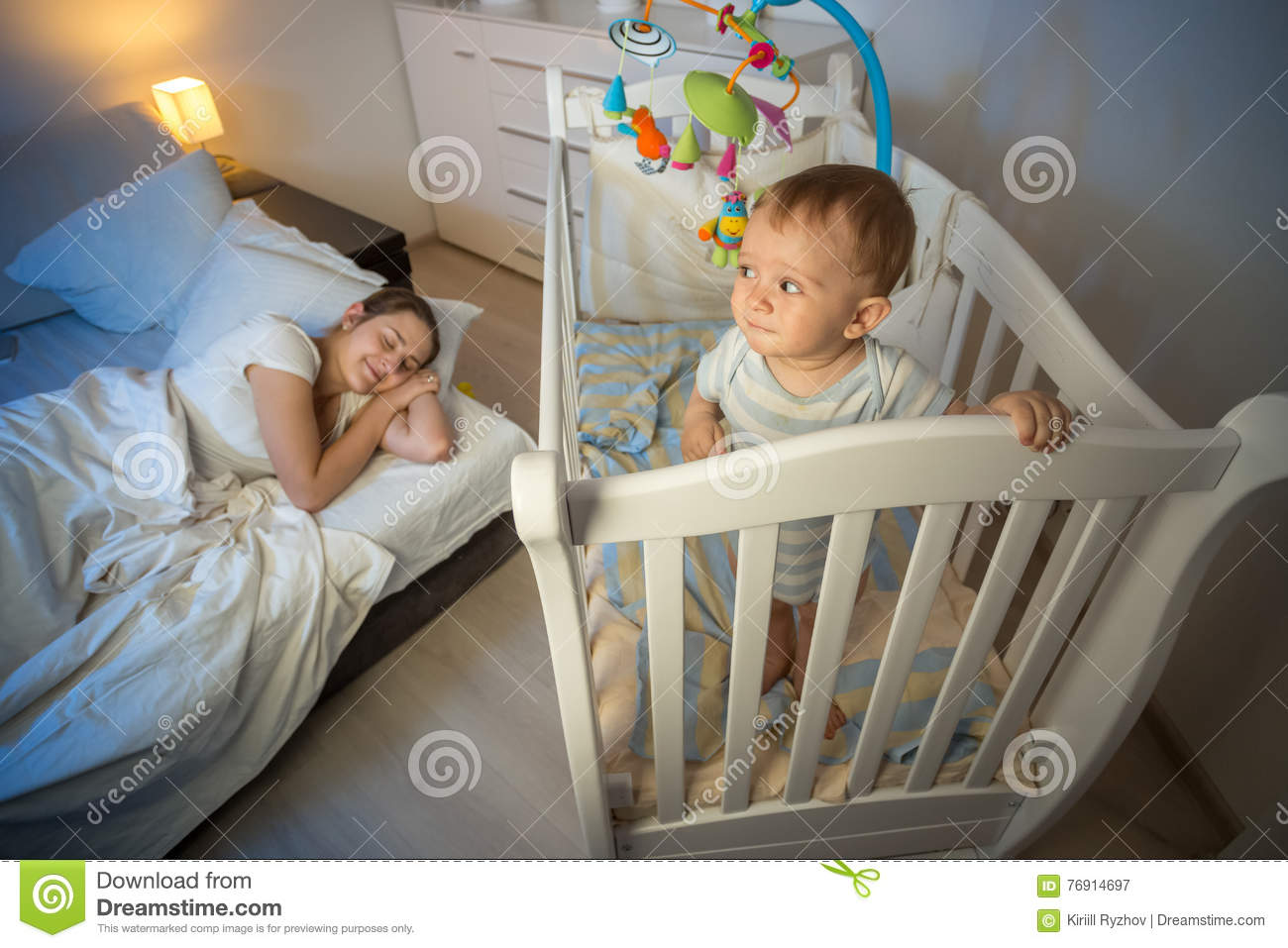 Portrait of baby standing in crib and looking at tired mother th