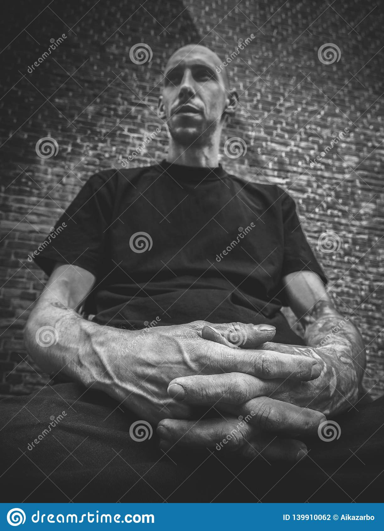 Portrait of a bald man with a brutal appearance and arms with tattoos in the foreground in black and white