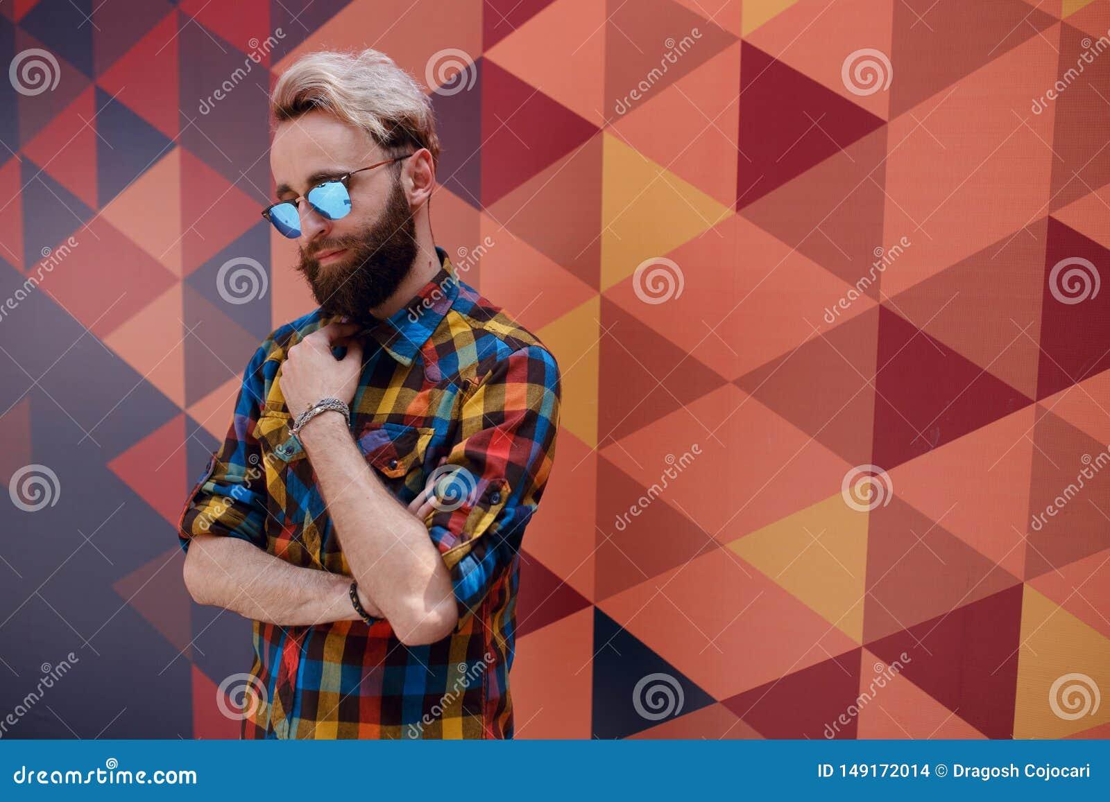 Portrait beau d un jeune homme de hippie, posant pr?s du fond de multicolore, habill? dans la chemise color?e