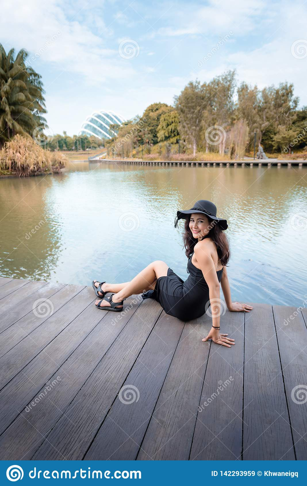 Portrait of Beautiful Asian Woman in Fashion Black Dress With Her Hat at Garden By The Bay, Beauty and Fashion Concept