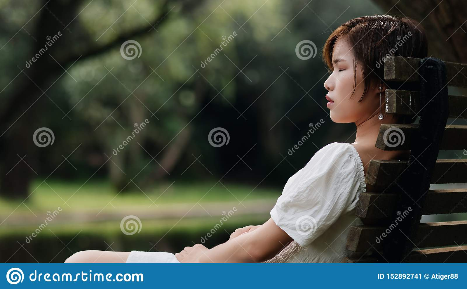Portrait of beautiful Asian woman sitting on bench in summer forest, Chinese girl in white dress sleeping with eyes closed