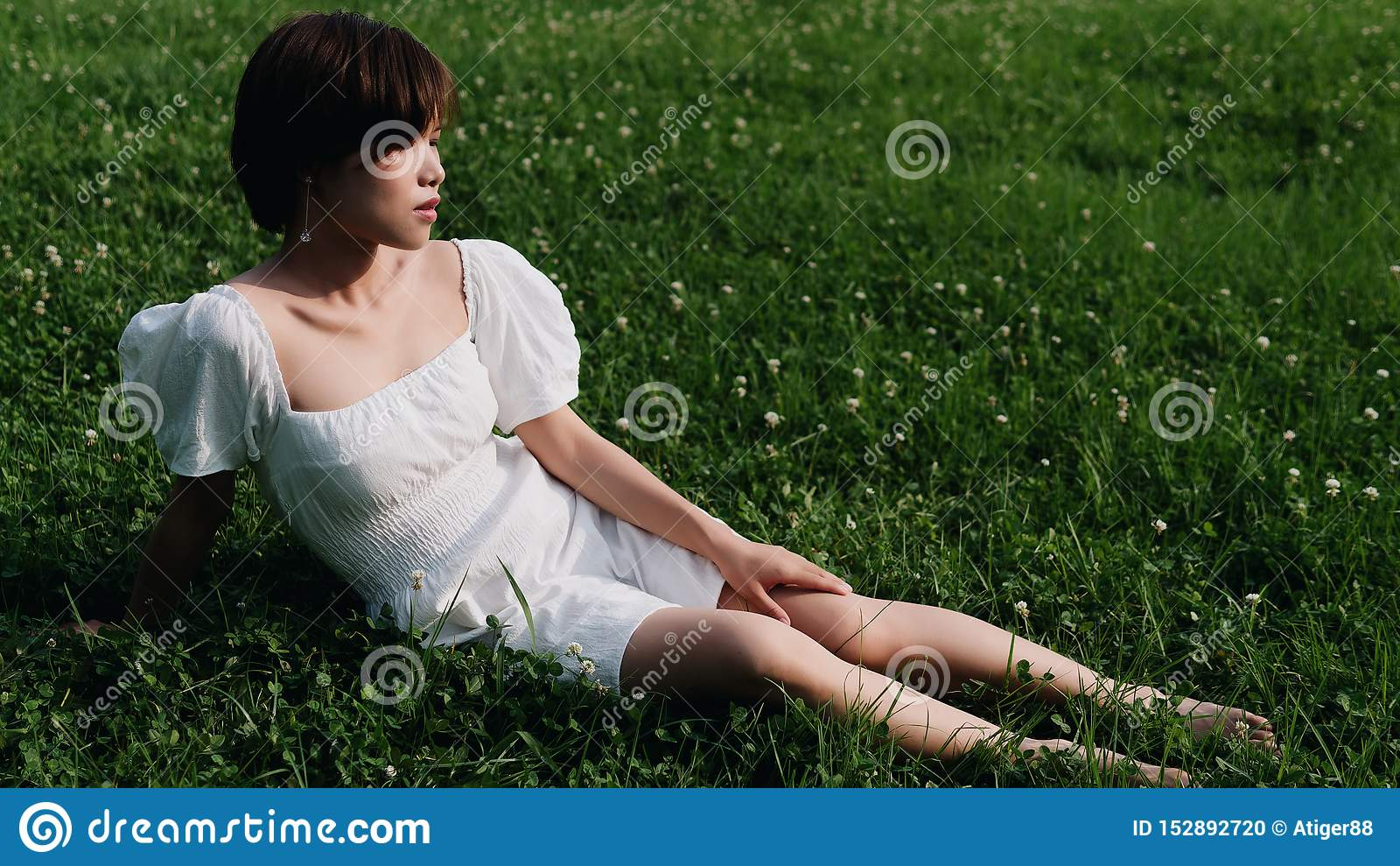 Portrait of beautiful Asian woman sitting on meadows in summer forest, Chinese girl in white dress sleeping with eyes closed