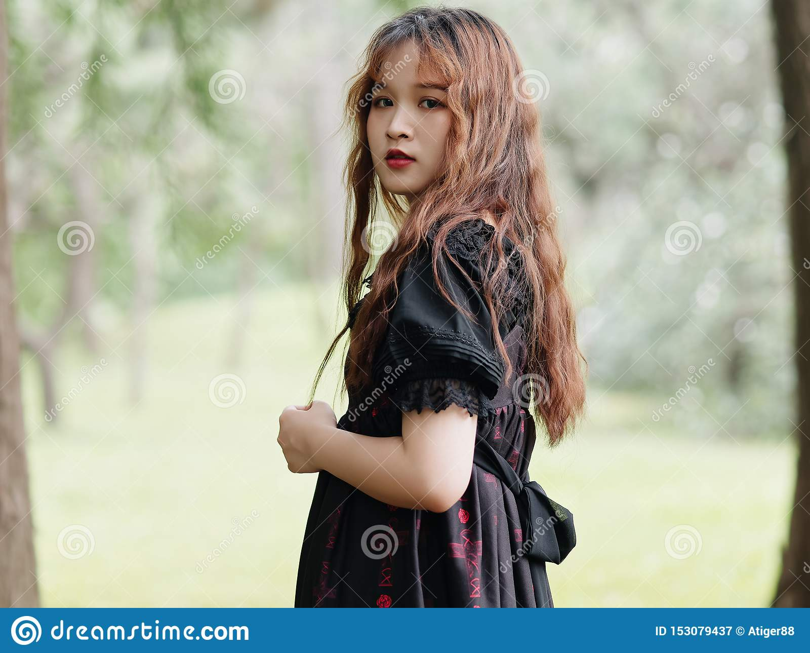 Portrait of beautiful Asian woman standing in summer forest, Chinese girl in vintage black dress looking at camera