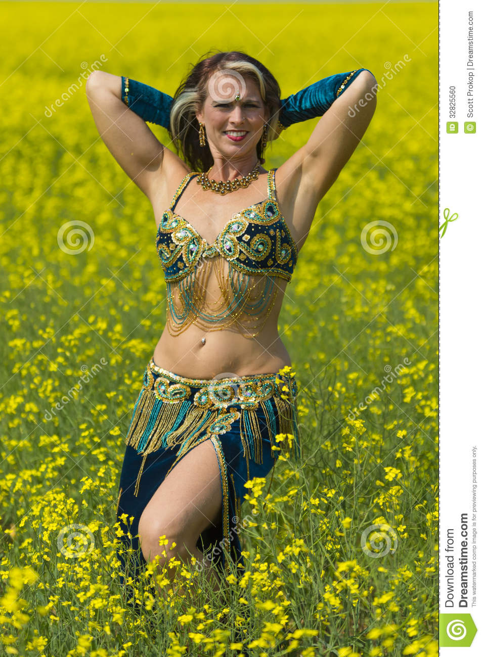 Young female belly dancer dressed in blue gold and white outfit in a