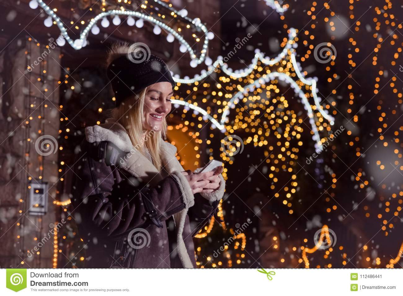 Portrait of beautiful blonde smiling girl using smart phone in f