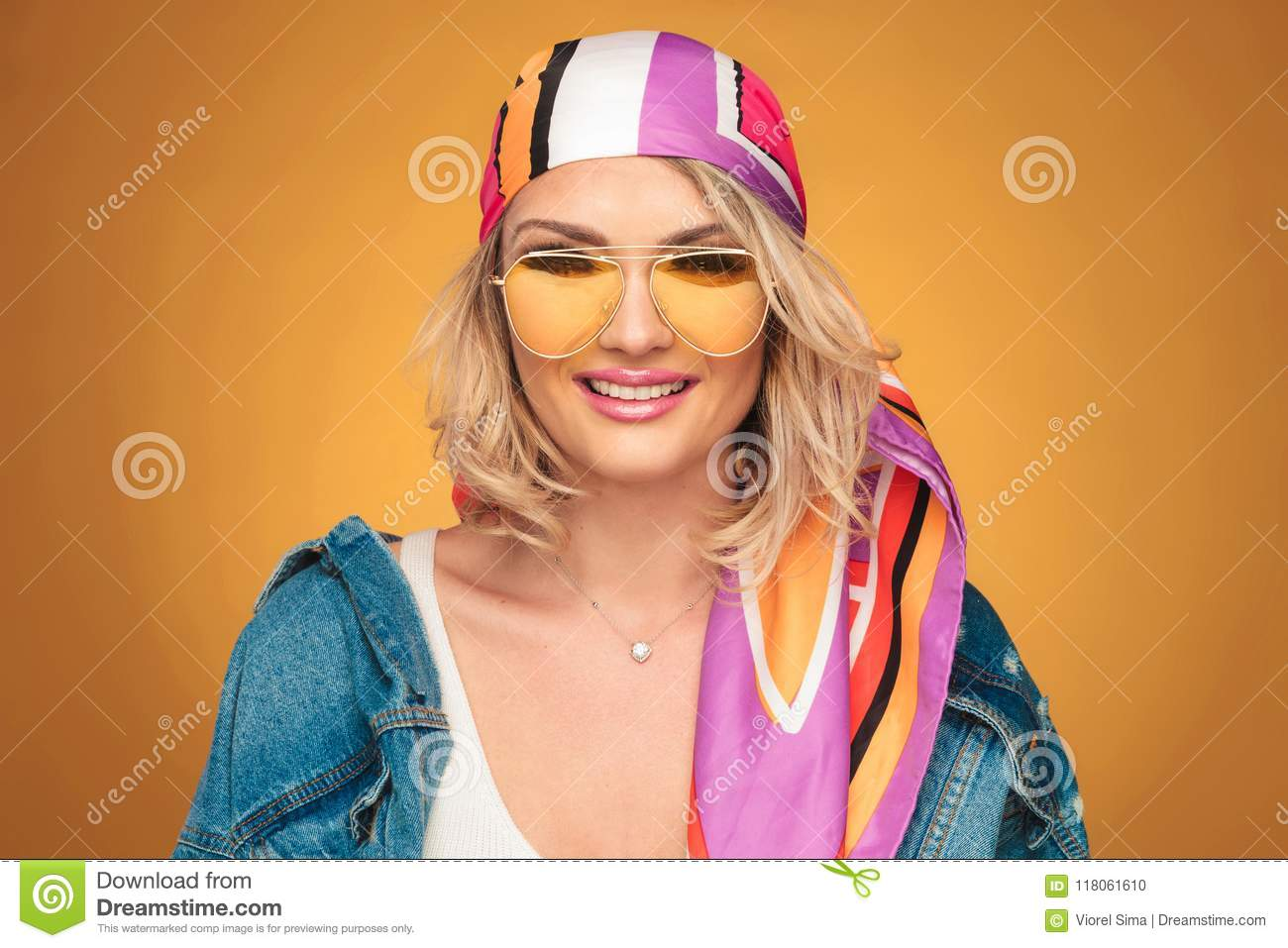 f3a80d9366 Portrait of beautiful blonde woman with colorful outfit smiling on yellow  background. She is wearing a colorful headscarf