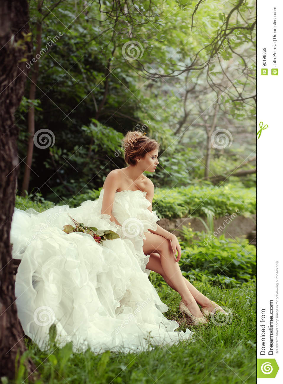 Portrait of a beautiful bride woman sits in a profile and looks into the distance.