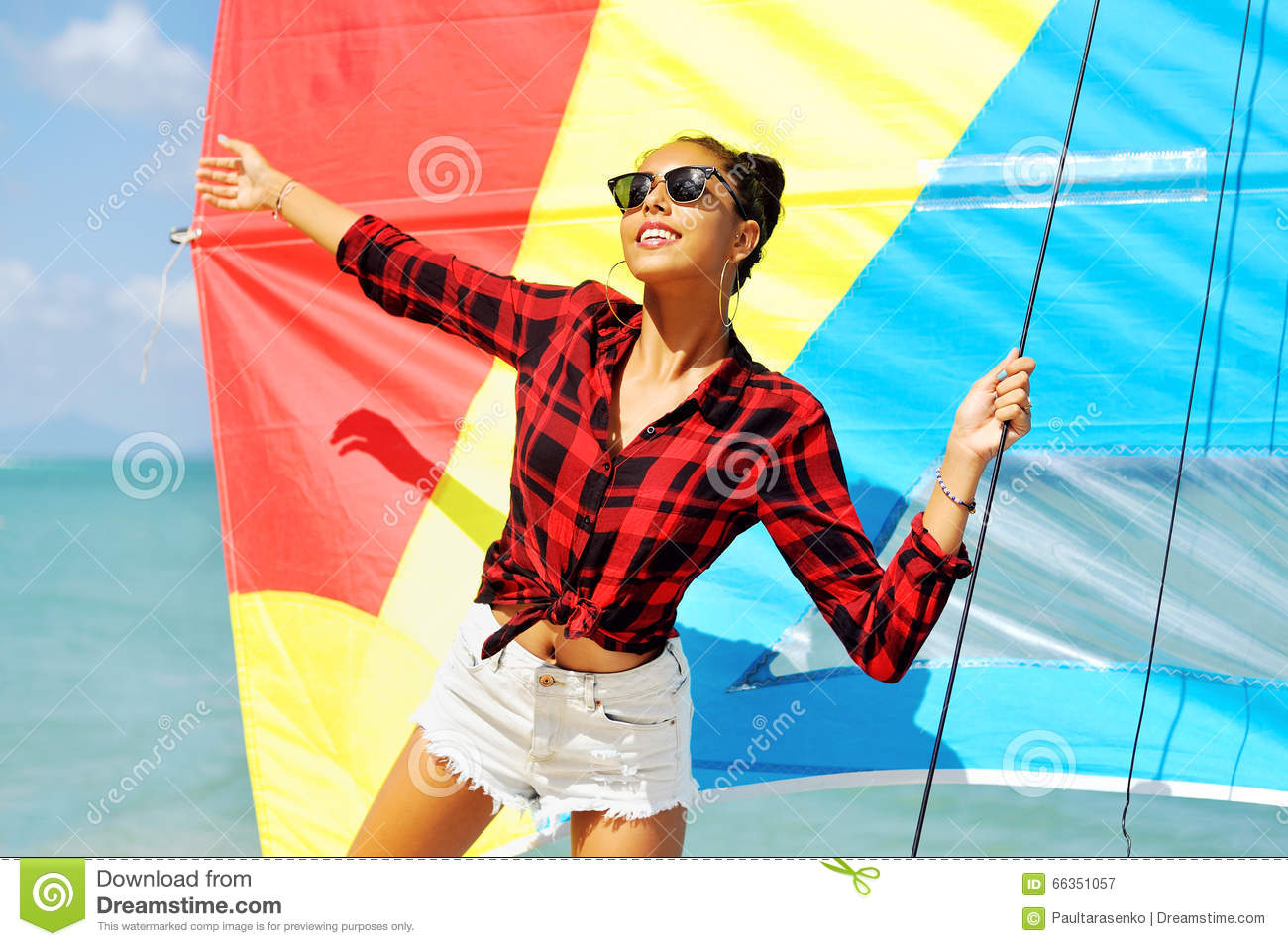 Portrait of beautiful brunette girl holds boat sails and smiling