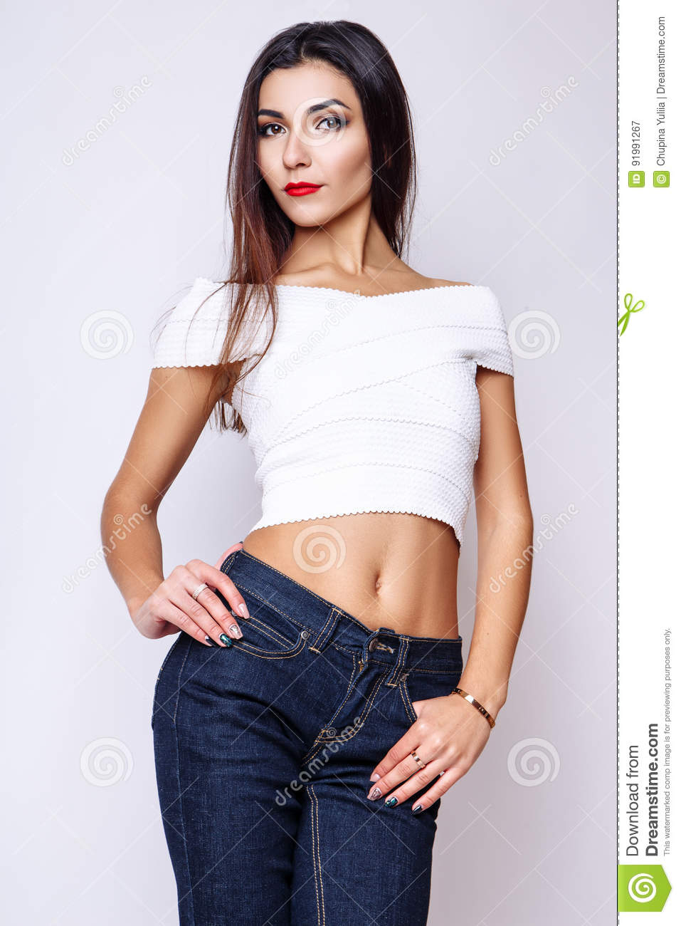Portrait Of Beautiful Brunette Woman In A White Blouse And Jeans
