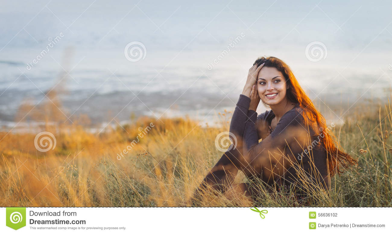 Portrait of the beautiful brunette woman at the windy autumn day