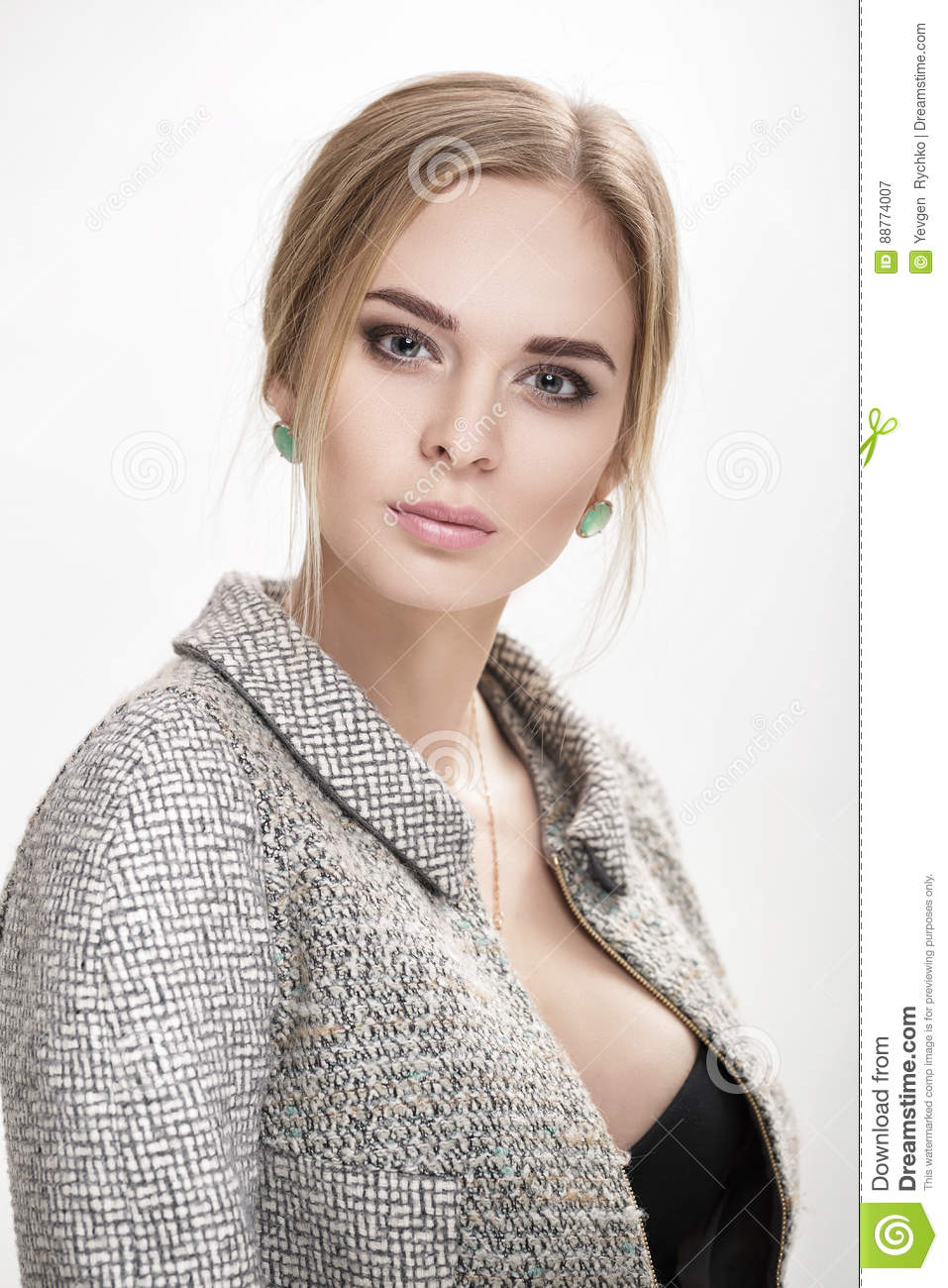Portrait of beautiful business woman blonde in black dress, jacket on gray background