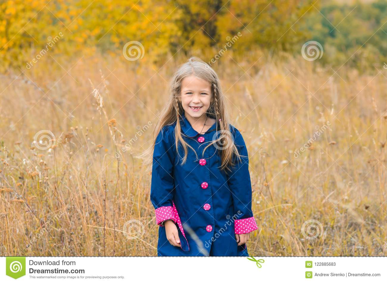 portrait of beautiful cute girl in clothes on background of autumn nature