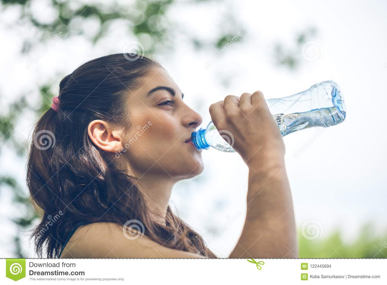 Portrait of beautiful dark-haired girl drinking water at summer