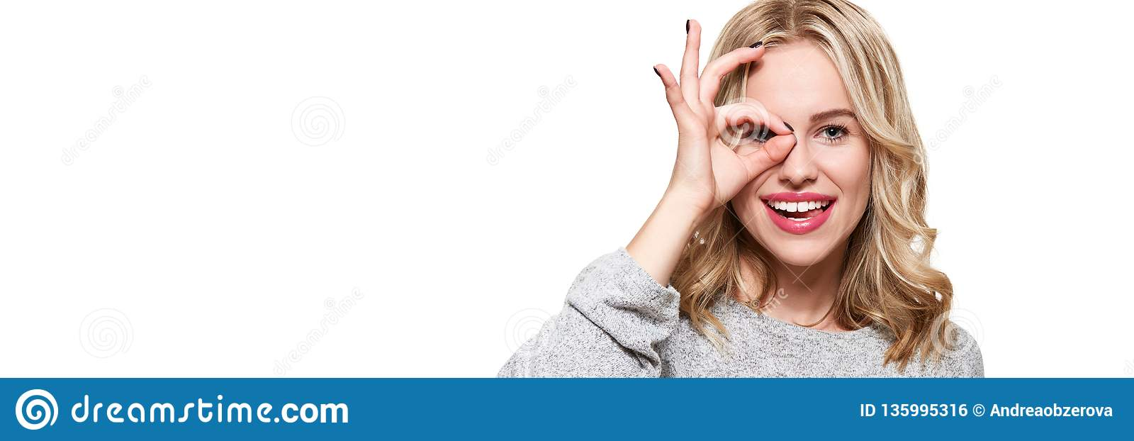 Portrait of beautiful excited woman in casual clothing smiling and showing ok sign at camera isolated over white background.