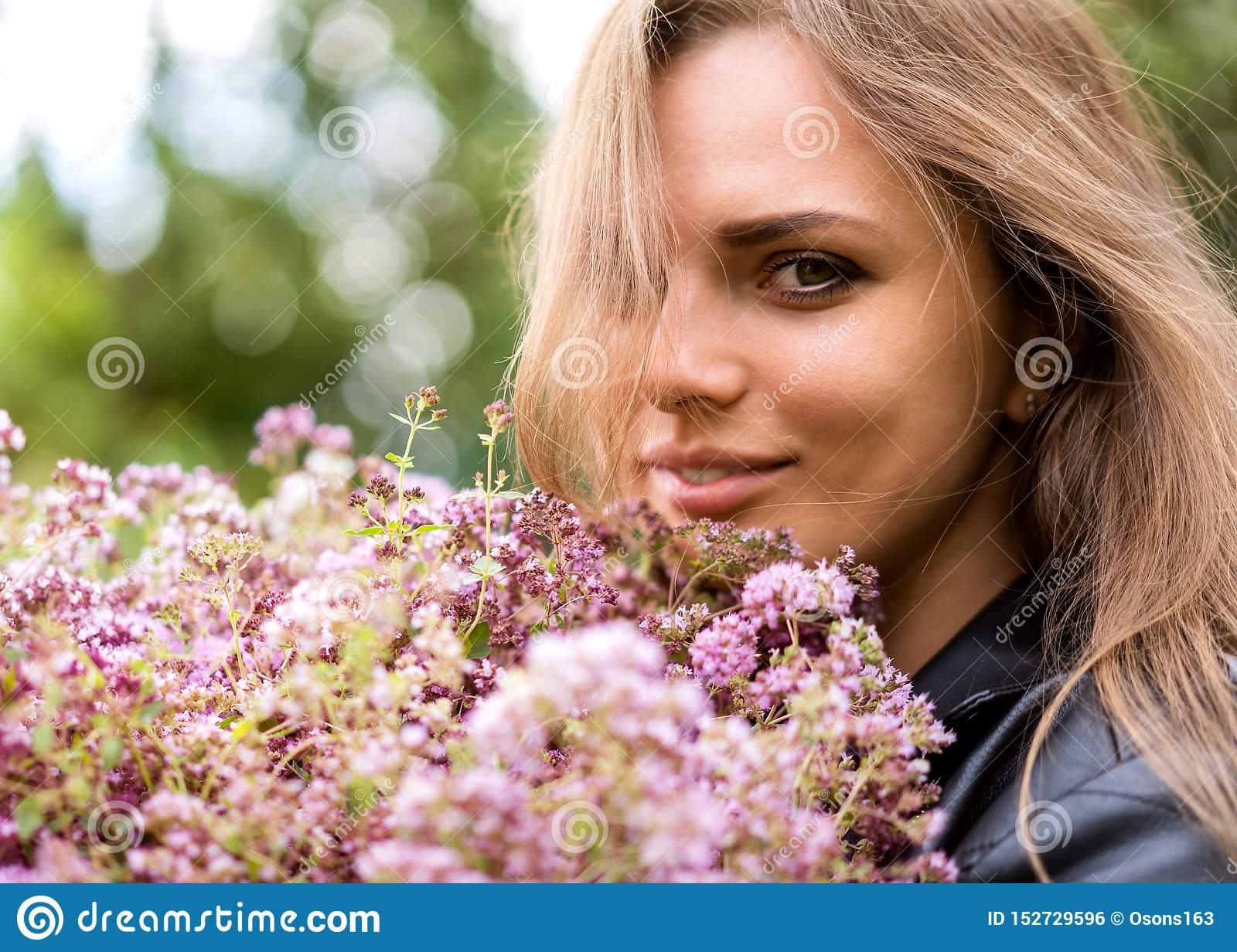 Portrait of a beautiful fashion girl with a bouquet of lilac flowers on the street