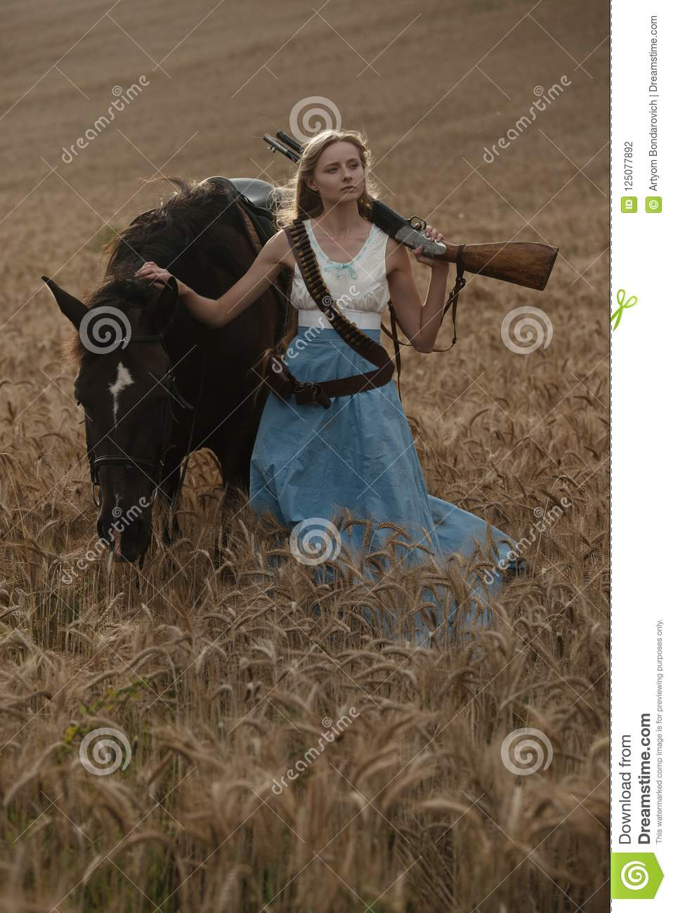 Portrait of a beautiful female cowgirl with shotgun from wild west riding a horse in the outback.