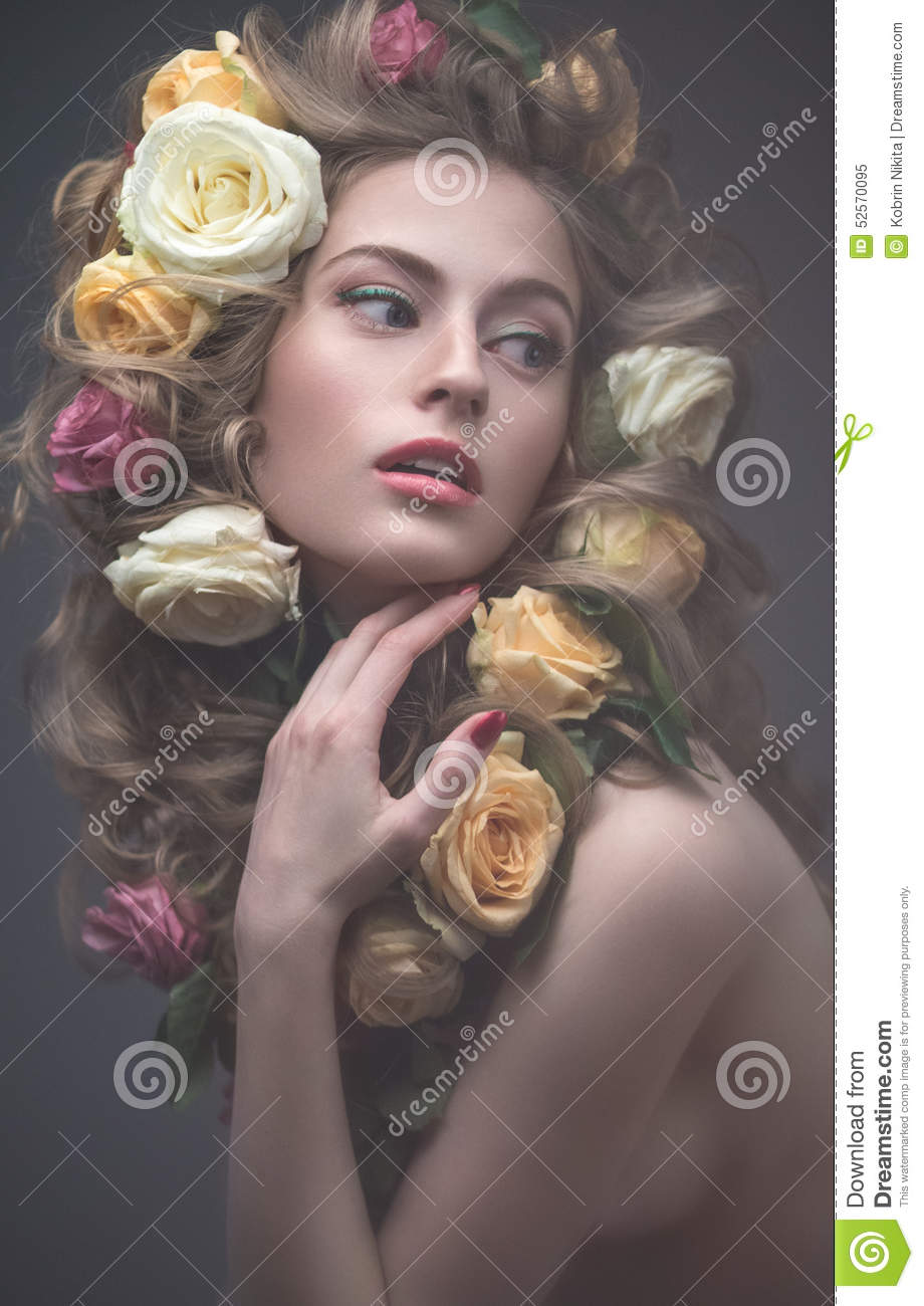 Portrait of a beautiful girl with a gentle pink make-up and lots of flowers in her hair. Spring image. Beauty face.