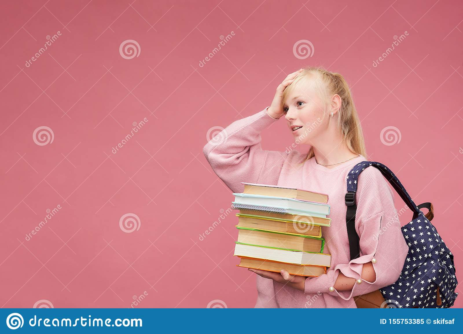 Portrait of a beautiful girl student with a backpack and a stack of books in his hands is smiling at the pink background