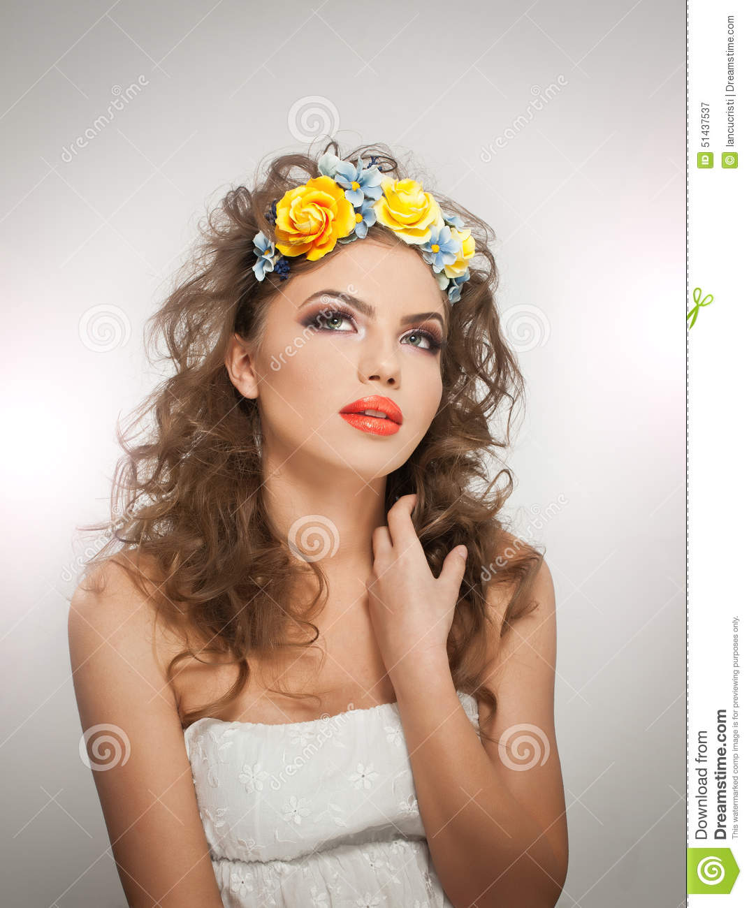 portrait of beautiful girl in studio with yellow roses in her hair