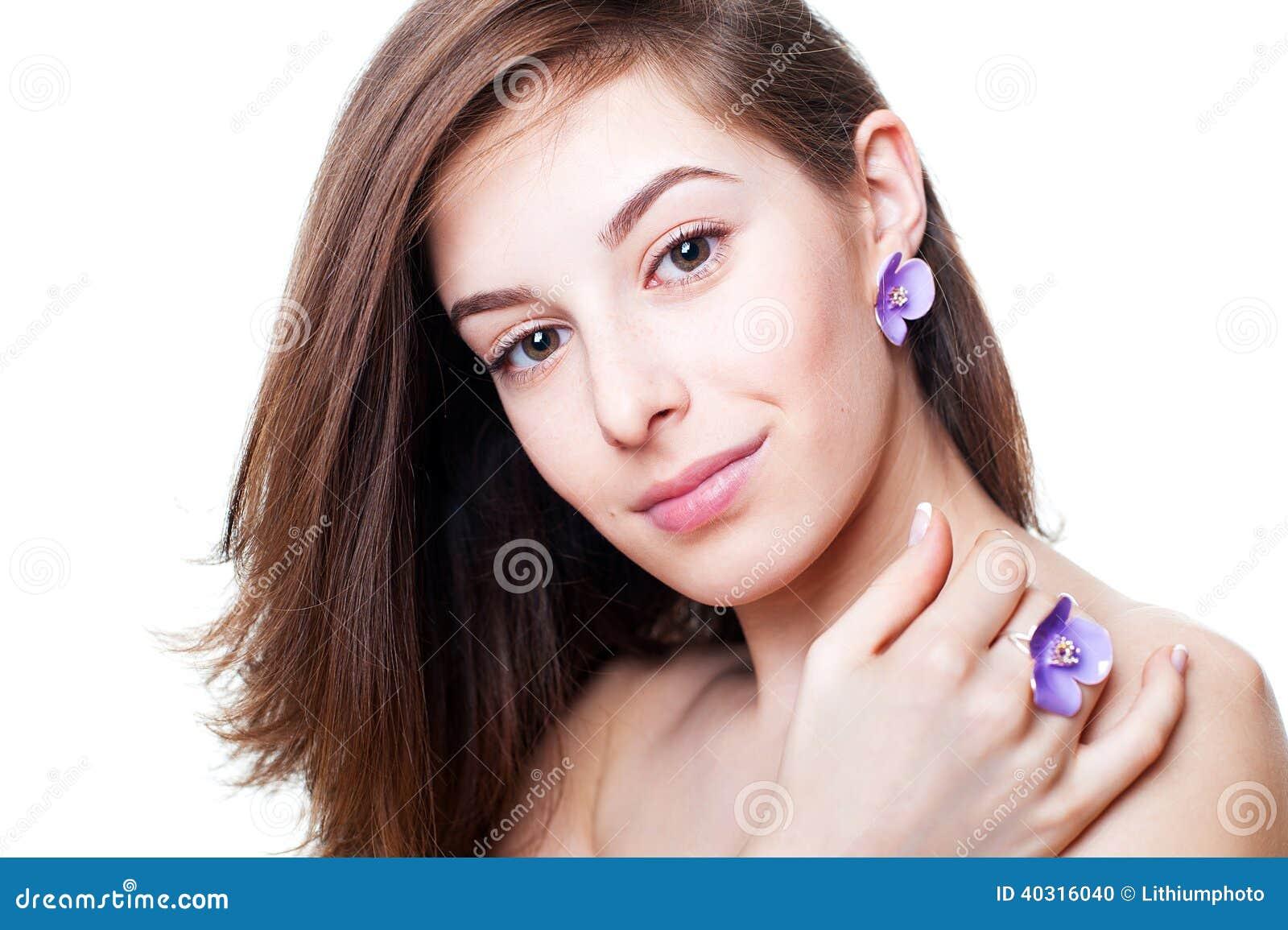 Portrait of beautiful girl with violet flower bijouterie