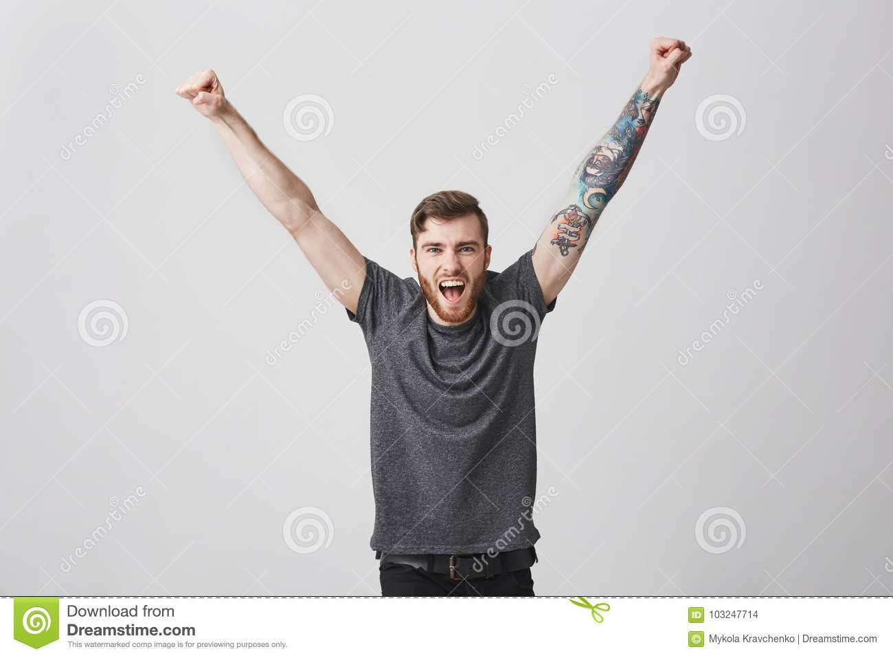 Portrait of beautiful happy encouraged caucasian man with beard and tattooed arm rising hands, screaming in full volume