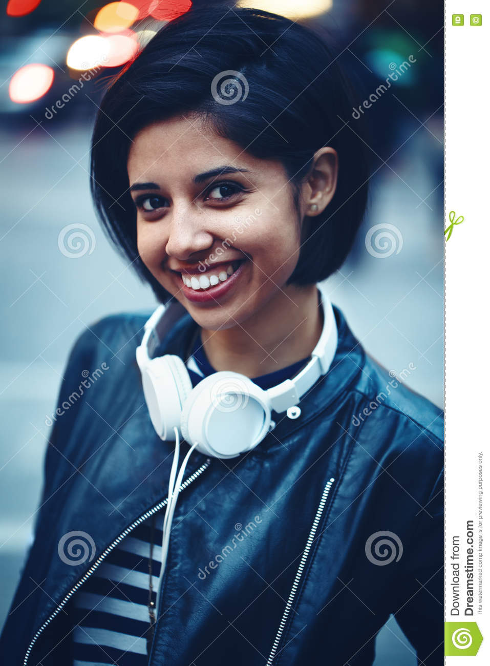 Portrait of beautiful Hispanic latino girl woman shor black hair in leather jacket with headphones outside in evening night city