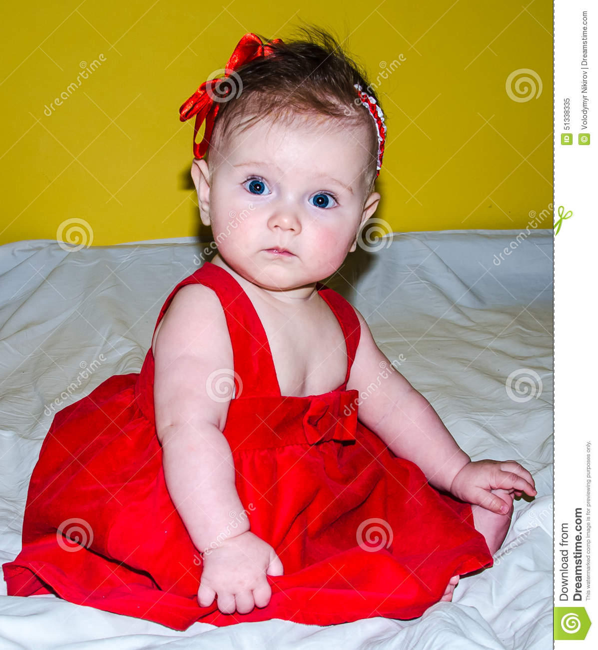 portrait of a beautiful little baby girl in a red dress with a bow