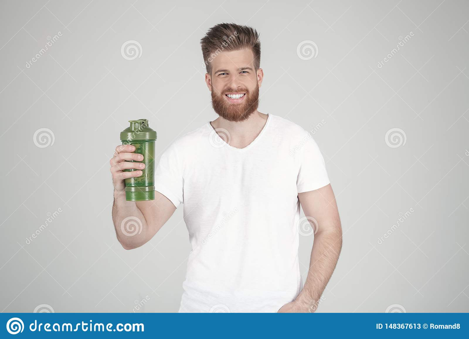 A portrait of a beautiful man with a beard and a fashionable hairstyle, dressed in casual clothing, holds a sports shaker and