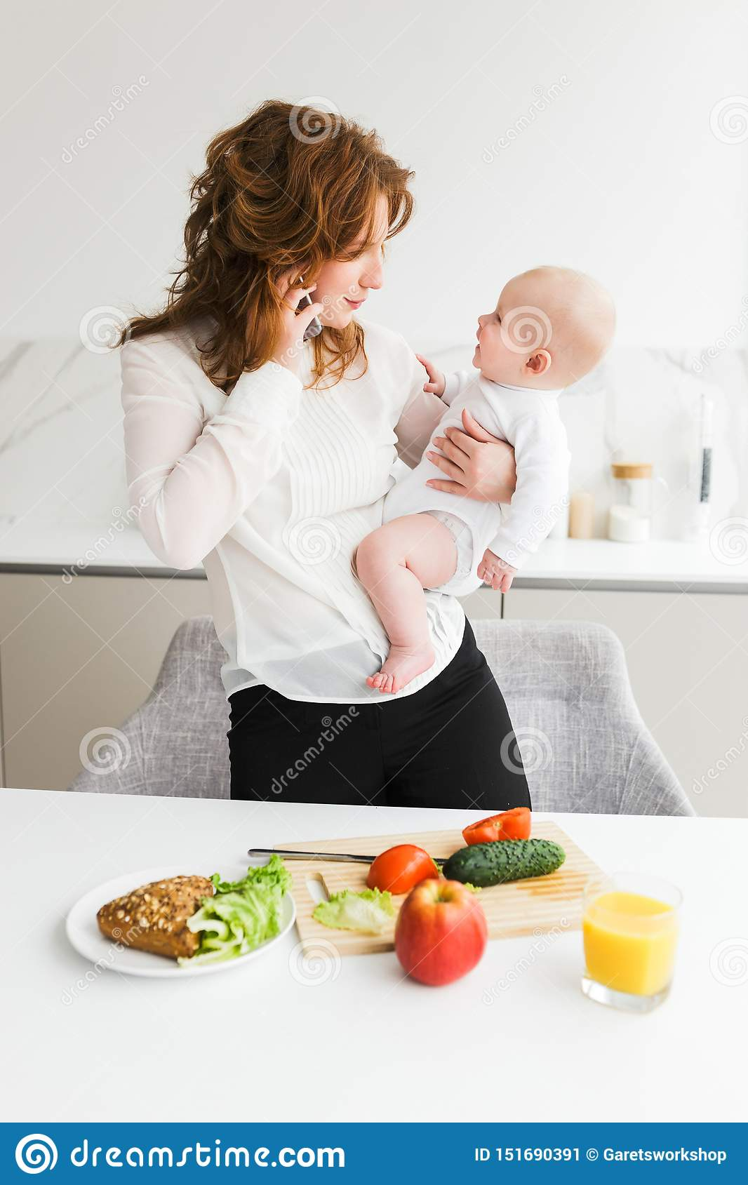 Beautiful mother holding her happy little baby while talking on her cellphone and cooking on kitchen