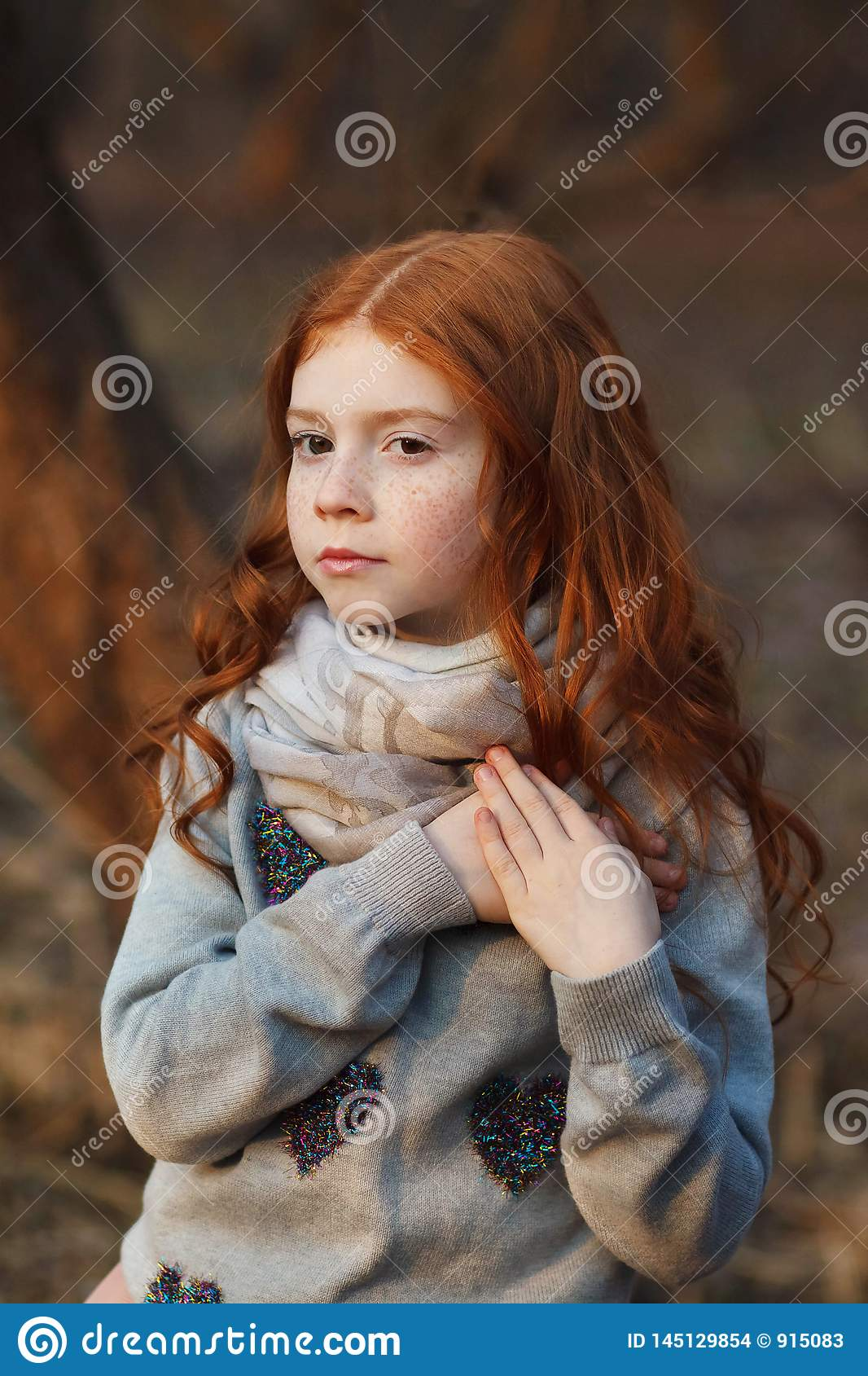 Portrait of a beautiful pensive girl with red hair and freckles