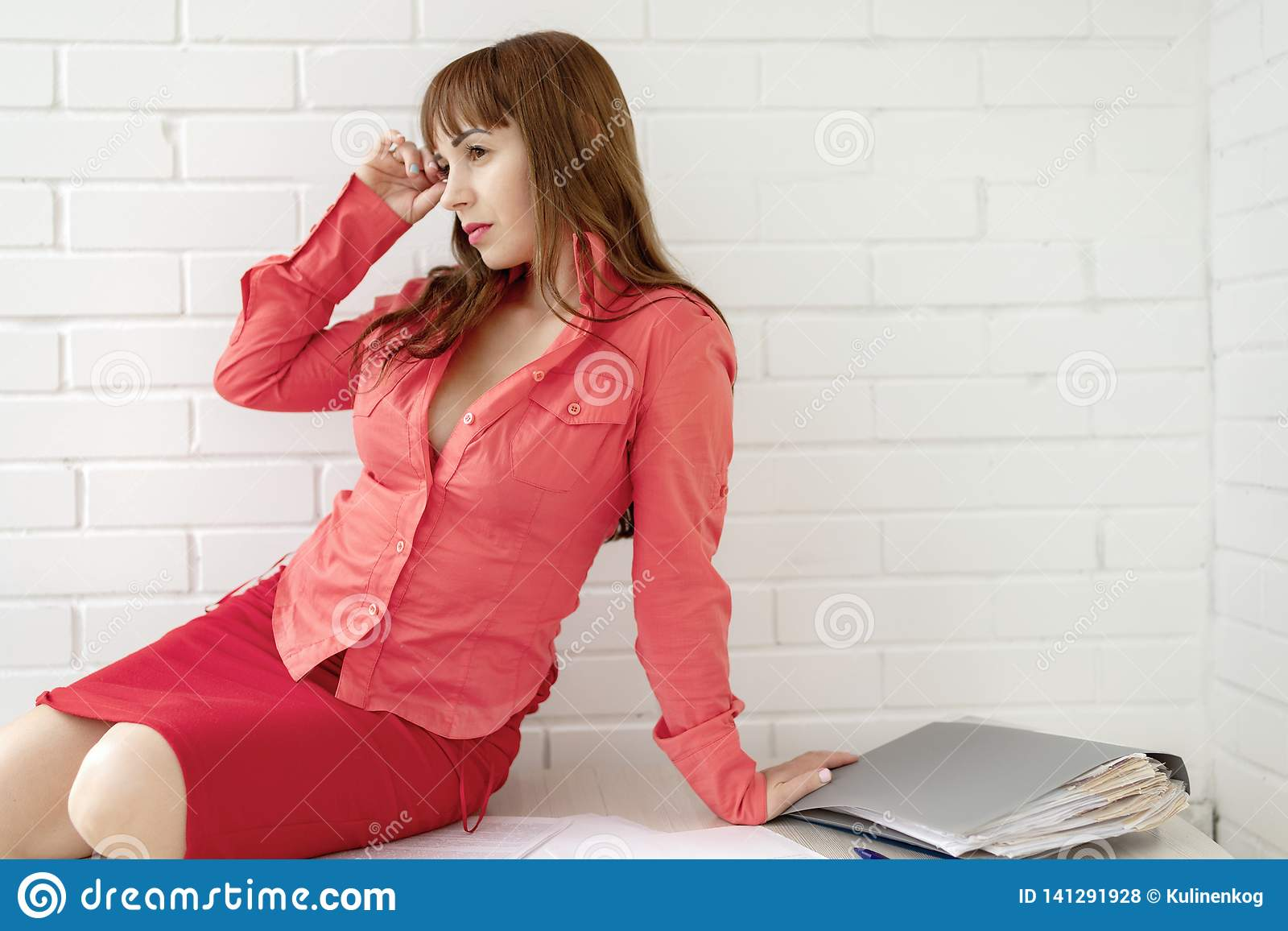 Portrait of a beautiful receptionist business girl sitting at desk on a white background