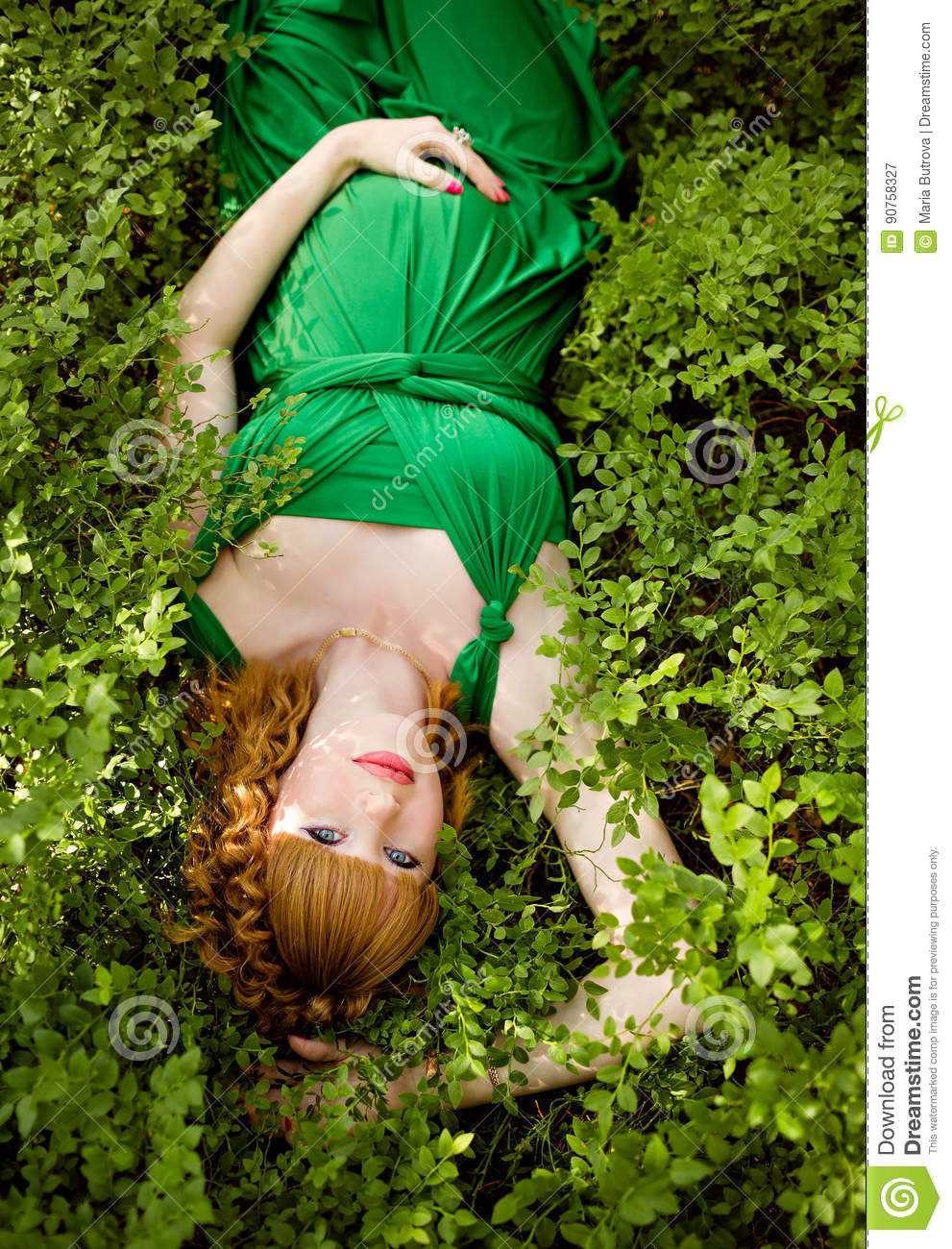portrait of a beautiful red-haired pregnant girl in a green dress, lying in the grass