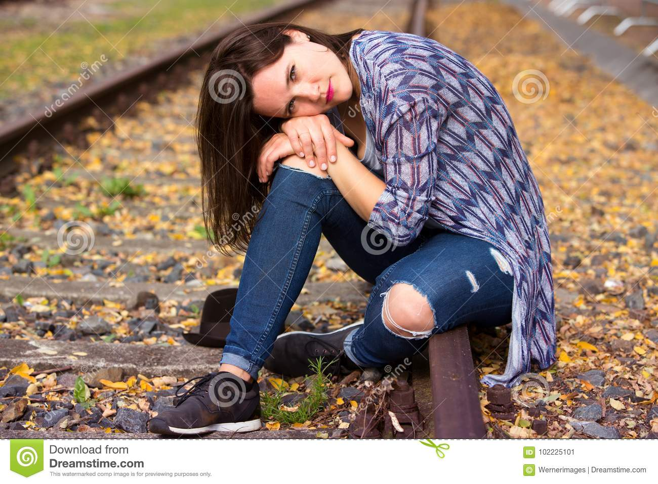 Sad Young Girl Sitting Lonely On Rail Track Stock Photo