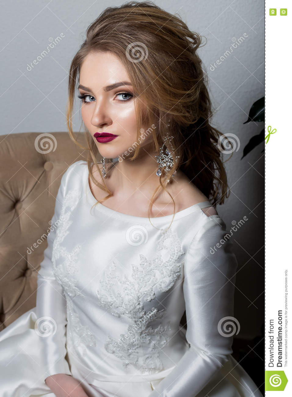 Portrait of a beautiful cute girl happy bride in an elegant dress with bright makeup in