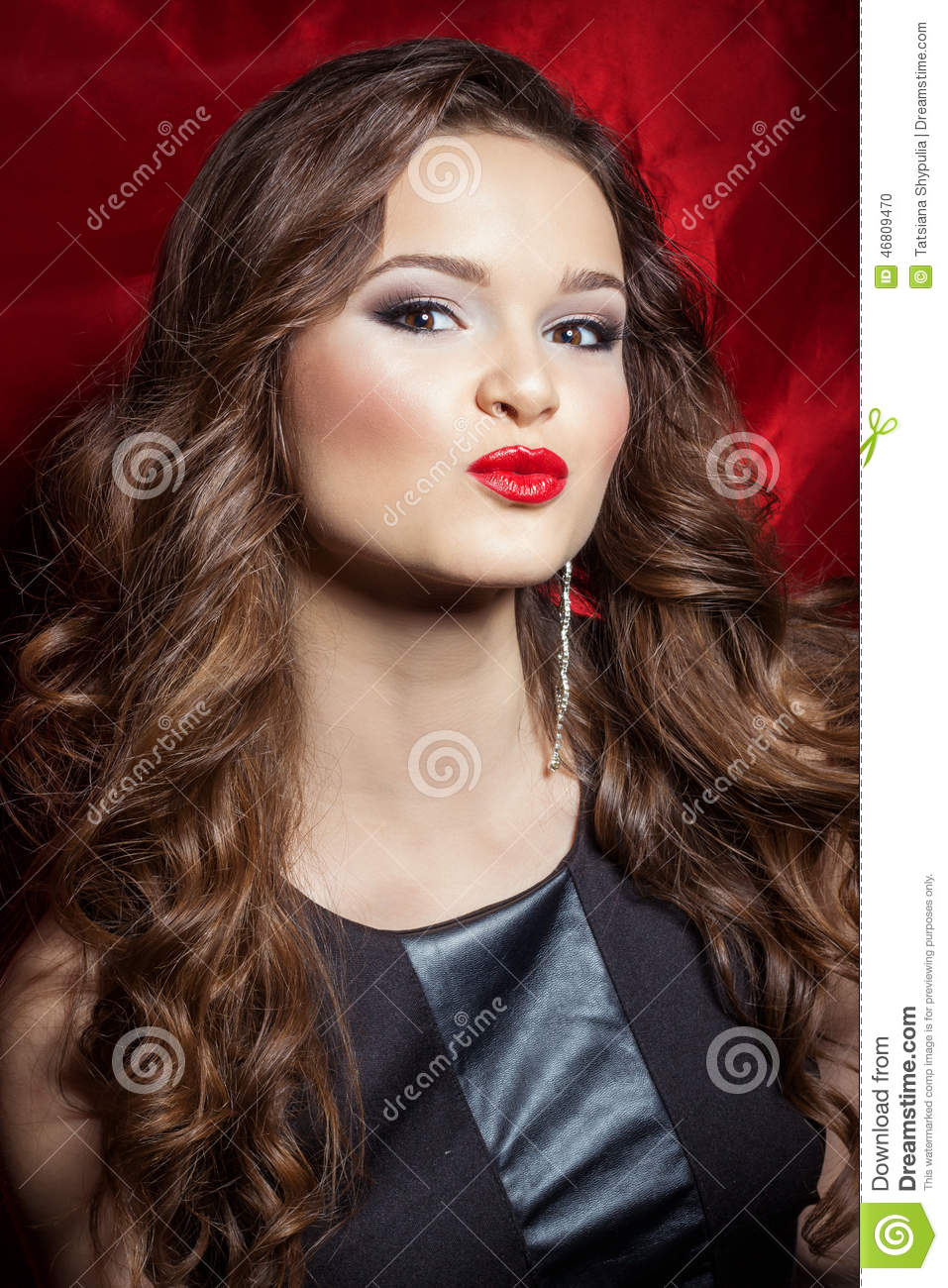 Portrait of a beautiful elegant girl brunette with long hair in evening dress with bright festive makeup and red lipstick